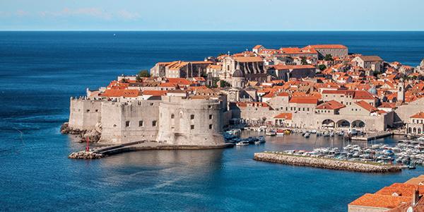 Photo de la ville de Dubrovnik et son port entourés d'eaux turquoises.
