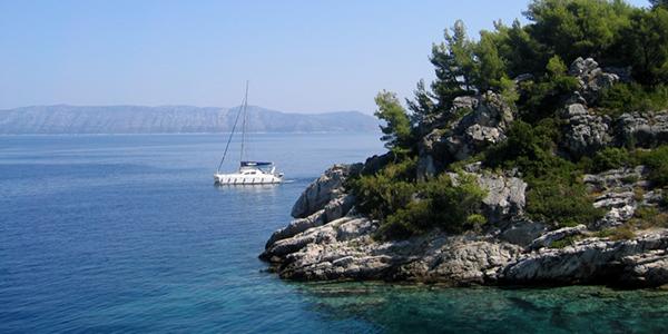 Photo de Sobra montrant une falaise et un bateau naviguant sur les eaux cristallines.