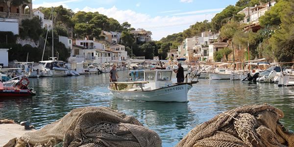 Photo du charmant port de Cala Figuera entouré de son village, où flotte un des bateaux au milieu de l'eau.