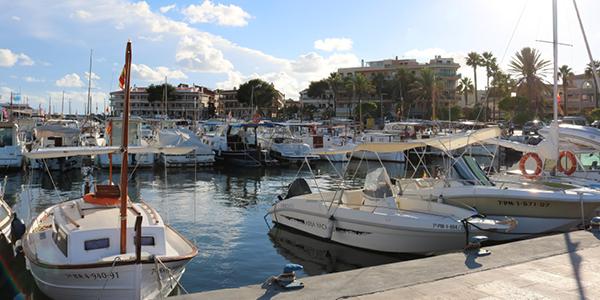 Photo du port de Colonia Sant Jordi avec de nombreux bateaux amarrés à quai.