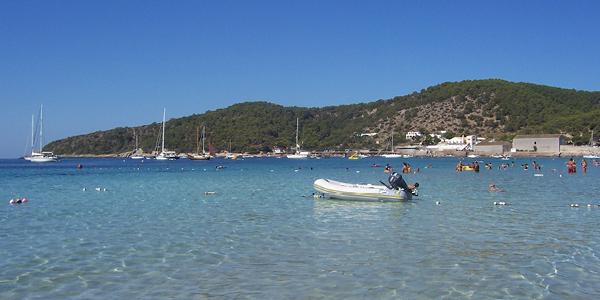 Photo de la plage de Ses Salines, où flotte un bateau à moteur dans l'eau transparente.