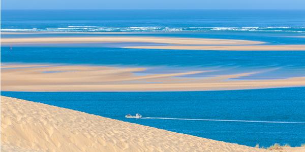 Un bateau naviguant devant la Dune du Pilat