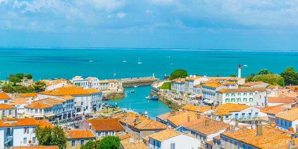 Les toits de Saint Martin de Ré à l'Île de Ré, ainsi que des bateaux naviguant au loin