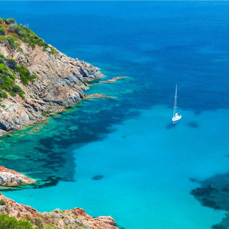 voilier naviguant sur les eaux turquoises en Corse