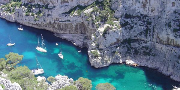 La calanque d'En-Vau où des bateaux naviguent sur les eaux turquoises.