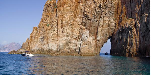 Un bateau naviguant à côté des grandes falaises des calanques de Piana