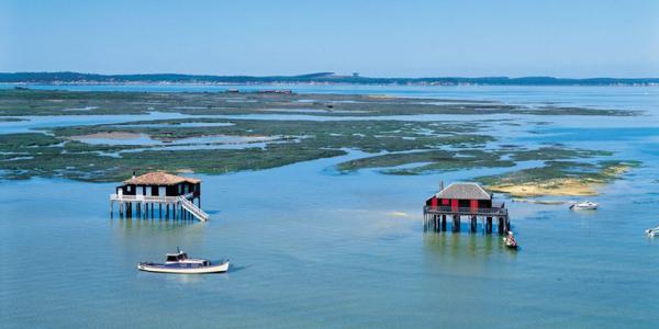L'île aux Oiseaux au bassin d'Arcachon avec des cabanes tchanquées et un bateau