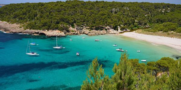 La plage d'eau turquoise de Trebaluger, à Minorque aux Baléares où naviguent quelques bateaux