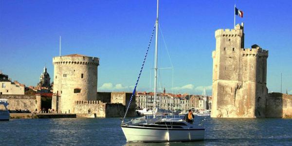 Un bateau naviguant devant les tours Saint-Nicolas et de la Chaîne à La Rochelle