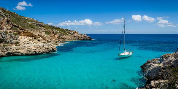 Un voilier naviguant sur une eau turquoise. Pourquoi réserver son bateau à l'avance