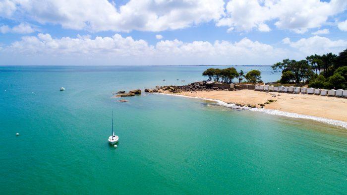 Vue de haut de l'île de Noirmoutier avec un voilier au mouillage dans une eau turquoise