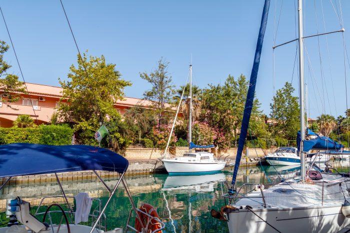 Voiliers blancs amarrés à la marina de Portorosa ,Sicile, Italie. En arrière plan une maison orange.