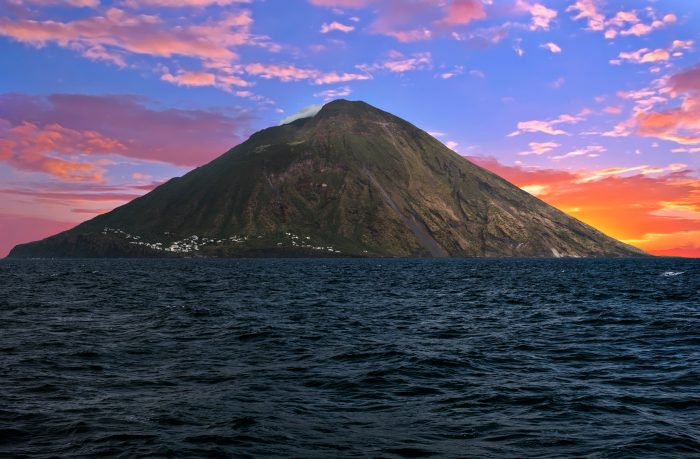 Vue depuis la mer de l'île volcanique Stromboli avec un coucher de soleil