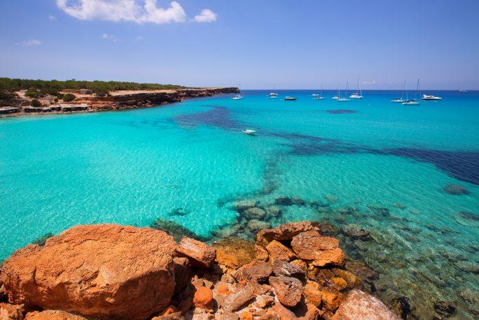 Cala Saona avec ses eaux translucides et son soleil avec en arrière plan des bateaux aux mouillages itinéraire de navigation d'une journée à Ibiza