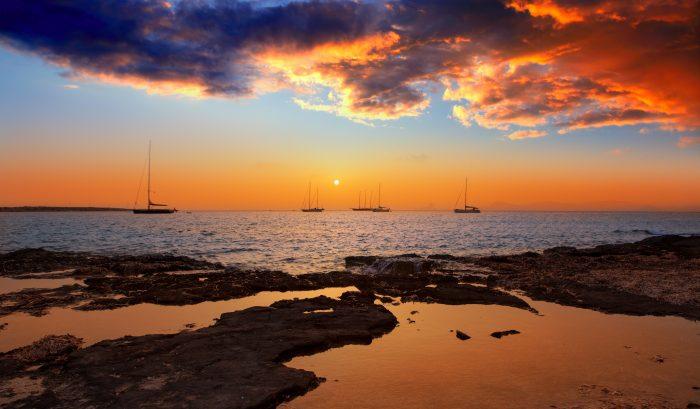 coucher de soleil coloré d'Ibiza vue de formentera avec Es Vedra avec au fond des bateaux aux mouillages itinéraire de navigation d'une journée à Ibiza