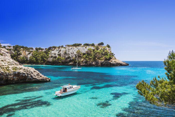 Cala Galdana sous un ciel bleu avec deux bateaux.  Deuxième escale de l'itinéraire de navigation à Minorque