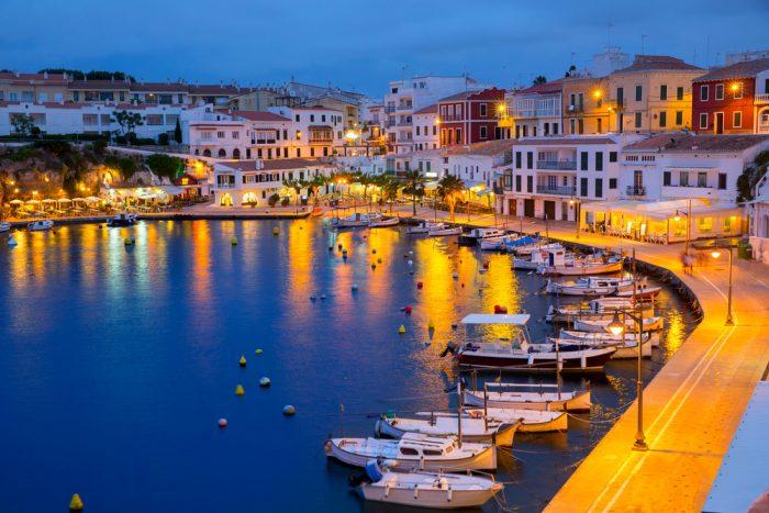 Port de Mahon de nuit avec les lumières de la ville reflétant sur l'eau et les bateaux.  Départ de notre itinéraire de navigation à Minorque.