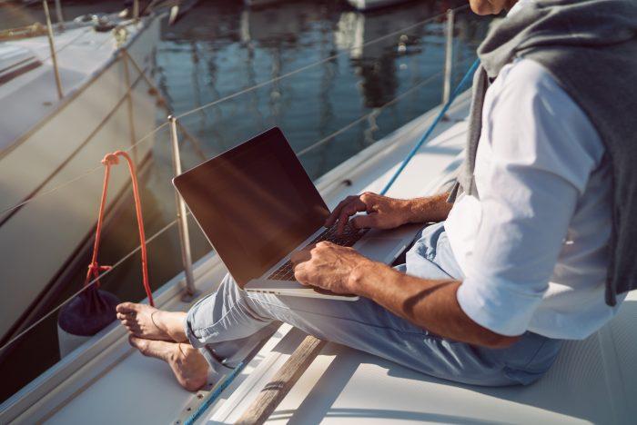Homme assis sur le pont d'un voilier avec son ordinateur lors d'un tour du monde